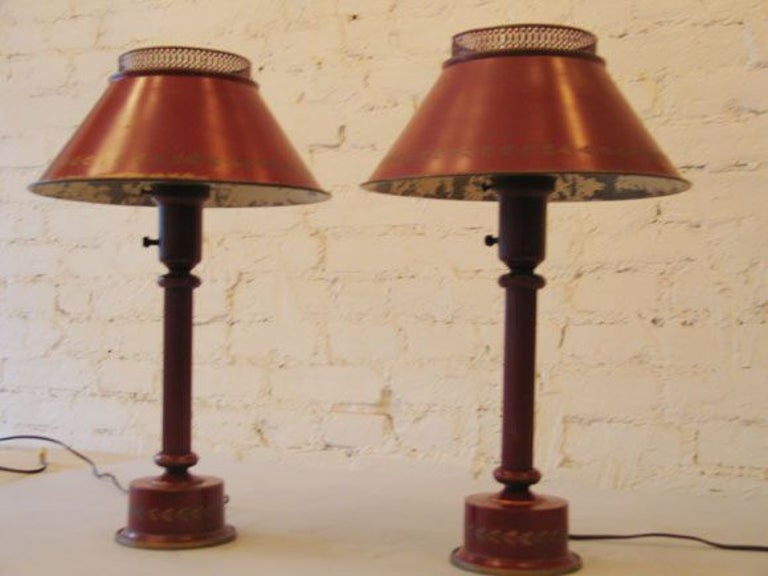Decorative pair of French midcentury painted tole lamps in a wonderful shade of red with gold leaf decoration near the border of the shade.  Priced and sold individually.