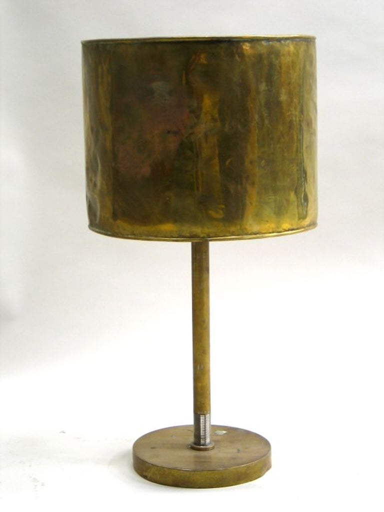 A French marine, industrial table lamp or desk lamp in solid brass with a hammered brass shade.The patina of the brass is naturally antiqued to a bronze color.  Provenance: Salvaged French ocean liner.