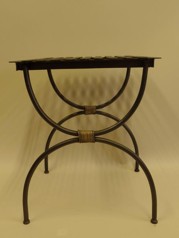 3 Pairs of French X-form iron side tables / luggage racks from the Mid-Century Modern period. The pieces, in matte black patina, are in the curile form with gilt iron wrappings uniting upper and lower halves. Convenient size and the strength of the