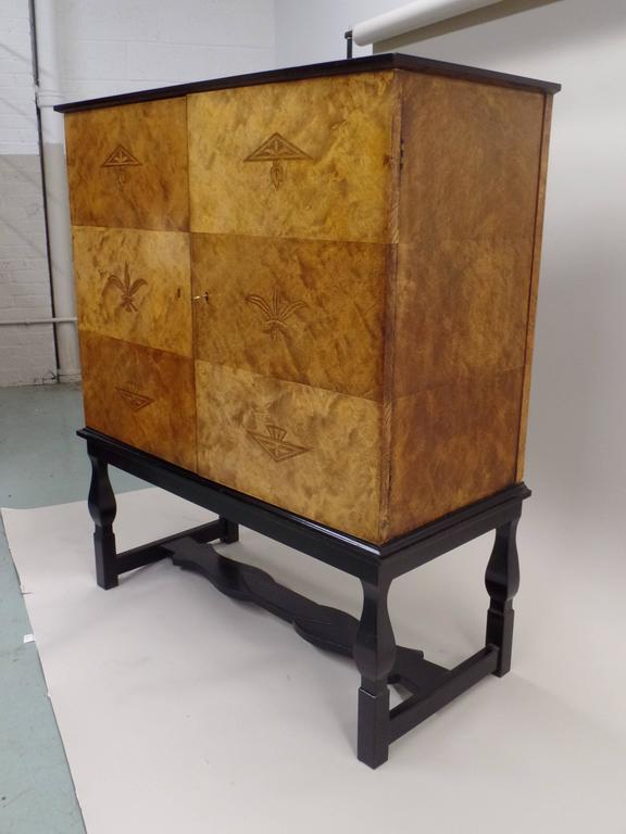 An important Swedish Grace / Mid-Century Modern Neoclassical cabinet, sideboard, buffet, bar, storage unit named 'Haga' by Carl Malmsten. The piece is in the modern neoclassical style, the cabinet sits on an ebonized base and it has inlays of