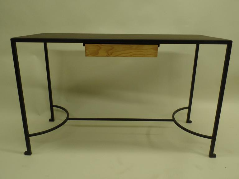 French Mid-Century console / desk attributed to Marc du Plantier in the modern neoclassical taste.  The piece is composed of hand wrought iron legs and base with an inset leather top and one wood pencil drawer. The delicate legs are united by a