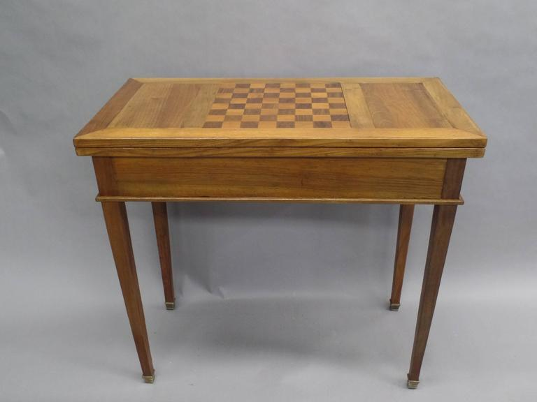A distinguished French modern neoclassical table in the Style of Louis XVI from the Mid-Century featuring a parquetry top made for chess and flip top made for playing cards. Tapered legs with bronze sabots extend to support the length of the