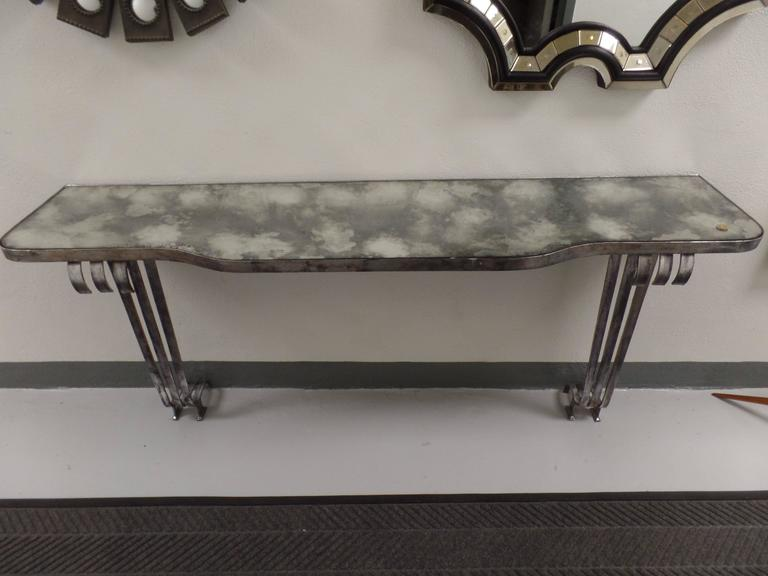 Elegant French 1930 modernist / post Art Deco wrought iron console by Raymond Subes.   The console is silver leafed with delicately patined, cloudy mirrored top.