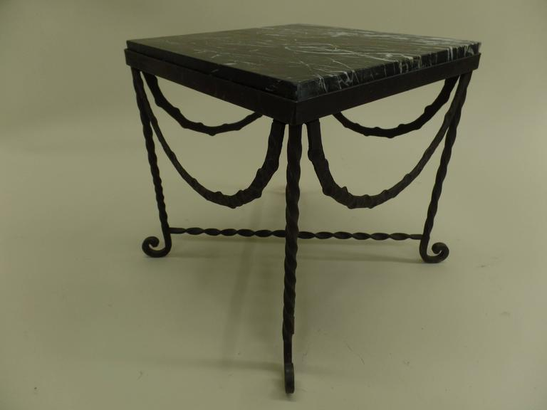 Rare, elegant pair of French Mid-Century hand-hammered forged iron end tables / nightstands / coffee tables. The pieces unite the neoclassical with the Modern and feature hammered iron garlands draping from each side of the table. These are typical