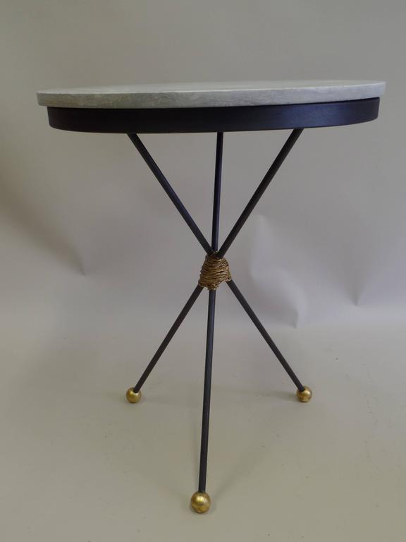 Elegant pair of French Mid-century partially gilt wrought iron tables with silver-grey travertine tops supported by a tripod base ending with three gilt iron ball feet.   The size of these tables allows them to function as side tables, end tables,