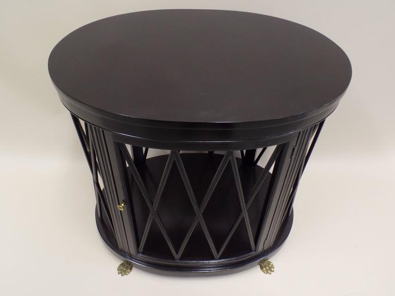 Elegant pair of oval form French Mid-Century Modern Neoclassical Ebonized Wood end tables / sofa tables by Maison Jansen.   The tables feature a stunning X-frame design around the circumference which allows transparent viewing completely through the