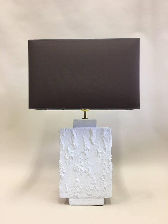 Elegant pair of French Mid-Century Modern plaster table lamps in the spirit of Alberto and Diego Giacometti. The pieces utilize rectangular geometric or architectural forms in contrast with a highly textured white plaster relief that create subtle