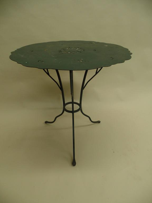 A unique pair of French Mid-Century end tables / gueridons, cafe tables in hand-wrought iron for use indoors or outdoors. The tables show the influence of Alberto and Diego Giacometti with the iron bases being hand-wrought in the form of a branching