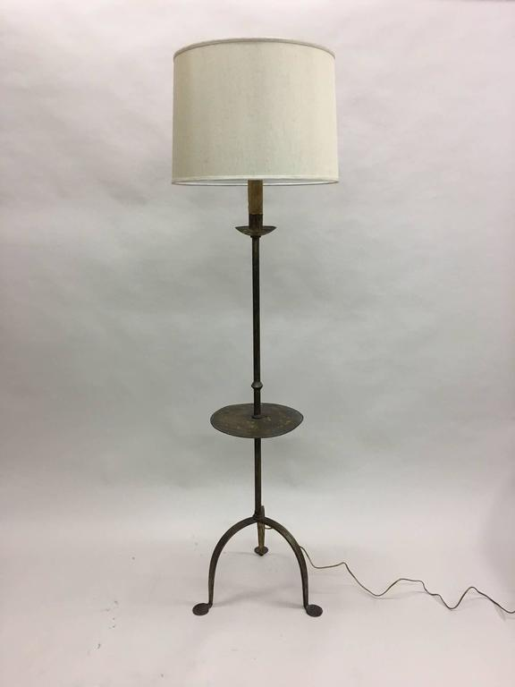 Stylish, elegant French, Mid-Century gilt iron standing lamp with an integrated circular side table. The piece features a tripod base with splayed feet. The gilt patina is gently worn.