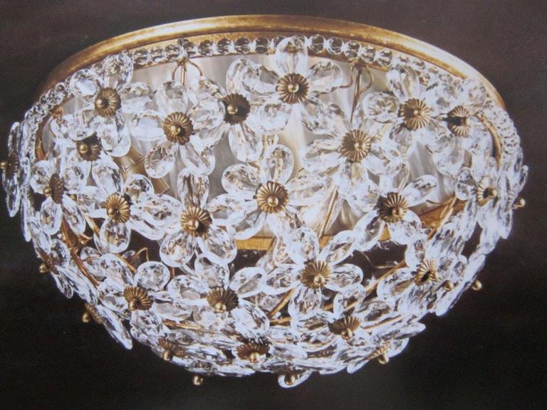 Pair of elegant Italian Mid-Century style flush-mounted ceiling fixtures composed of hand-cut solid Murano glass crystal flowers set in a gold-leafed frame. Each floral pedal is delicately cut. The toning of the gold leaf is soft enhancing the