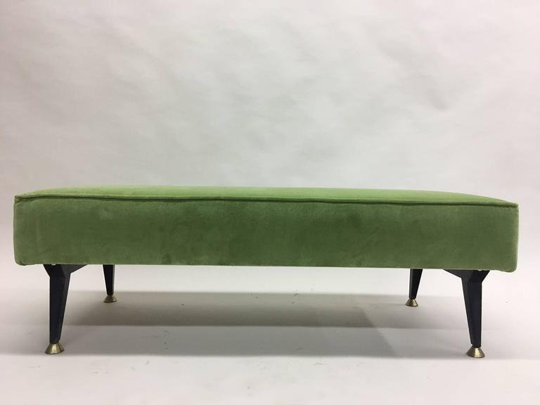 Elegant Italian Mid-Century Modern bench in the style of Osvaldo Borsani featuring four saber form and tapering black enameled metal legs ending in solid brass sabots. The piece is low to the ground, sleek and chic!