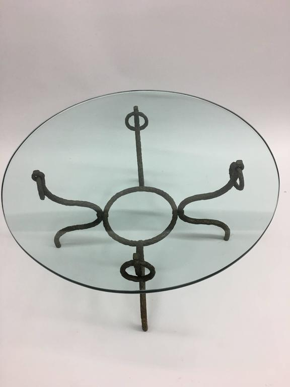 An elegant cocktail table in deeply hammered iron with bronze in the style of Giacometti. The stunning piece combines a spare Modern feel with Neoclassical spirit and features large ring pull decorations at each corner.  The piece is reminiscent of