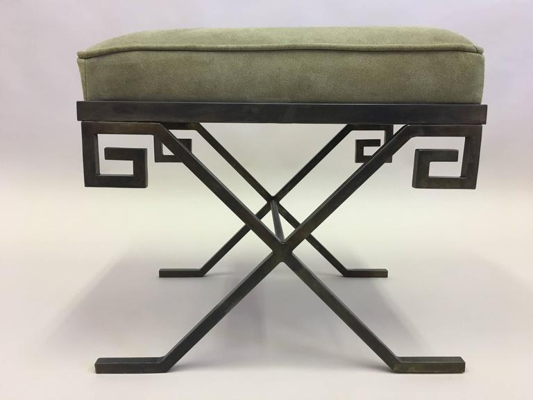 Elegant pair of stools or benches in bronzed wrought iron in the modern neoclassical taste expressed by Jean Michel Frank. The wrought iron frame is in the Classic X-form and the apron is in the form of a Greek key design.