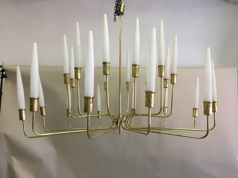 Very large, elegant Italian Mid-Century chandelier / pendant by Stilnovo with a solid brass frame and 24 satin glass candles set in multi-tier structure and in a modern neoclassical arrangement with perfect order and symmetry. 