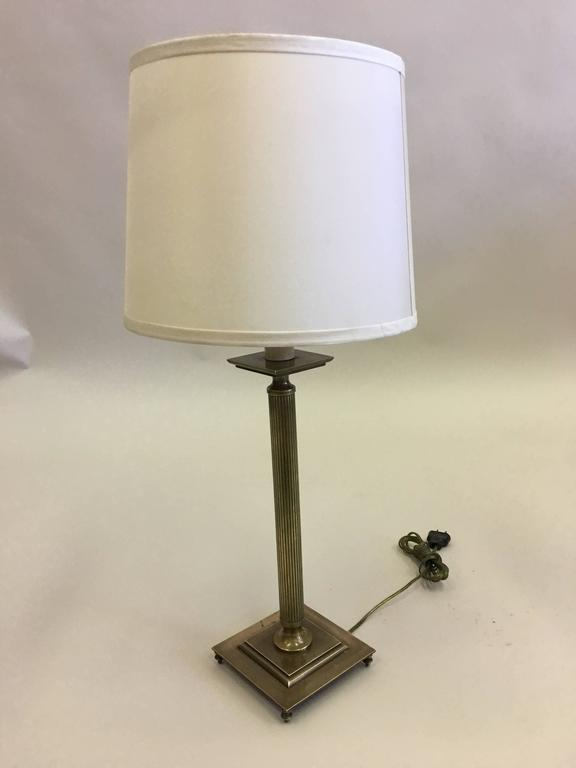 Elegant pair of French solid brass table lamps in the modern neoclassical tradition with fluted brass stems and raised brass square base resting on delicate brass finials. The pieces have a naturally aged antique brass patina.