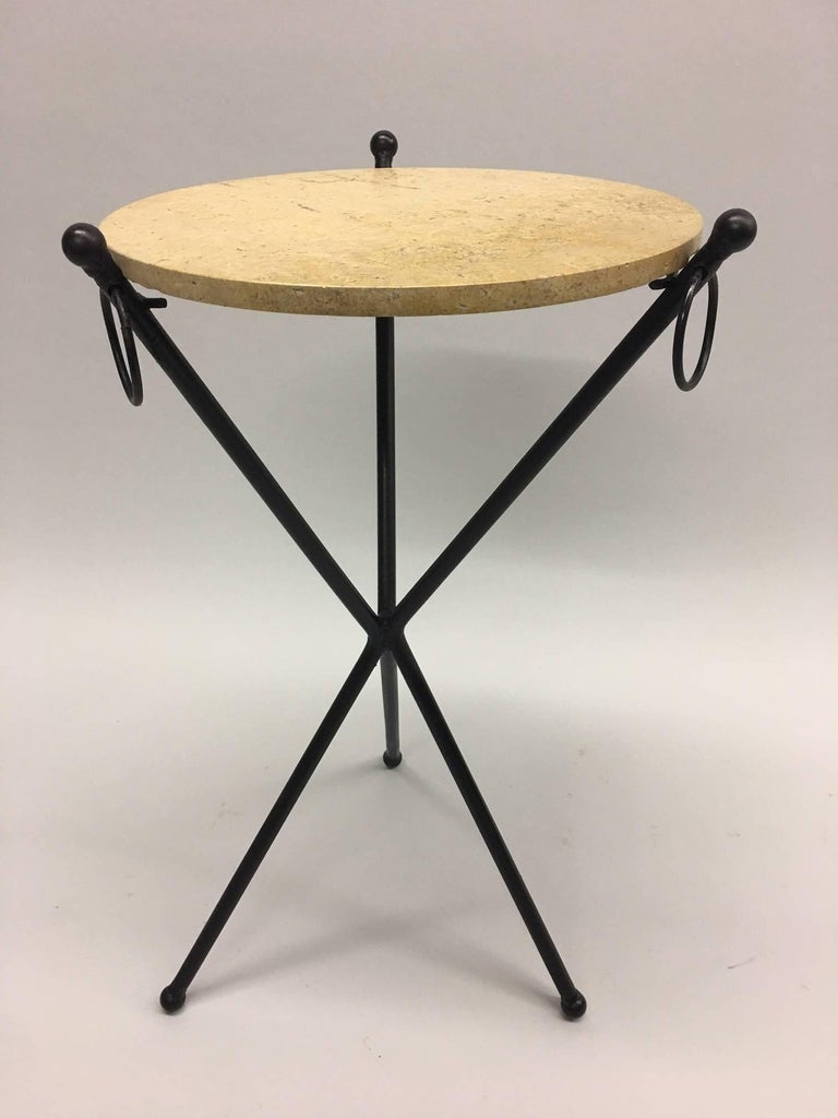 Two Frenchend tables/nightstands/gueridons composed of hand-wrought iron with black patina in the style of Jean-Michel Frank. The pieces have a sleek tripod form, elegant ball feet and finials. They feature three ring decorations. The top shown is