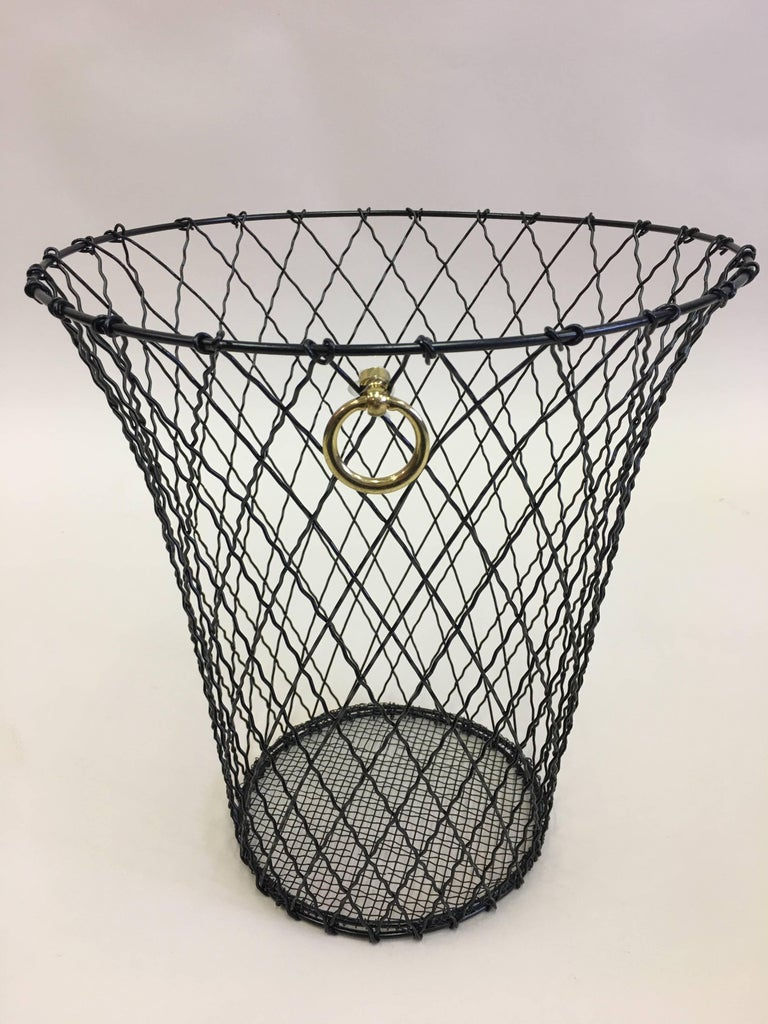 Two French trash baskets or wastebaskets that elegantly combine modern, neoclassical and industrial aesthetics. The pieces are composed of black enameled wire woven in a classic cross-hatched pattern completed by a solid brass ring pull.