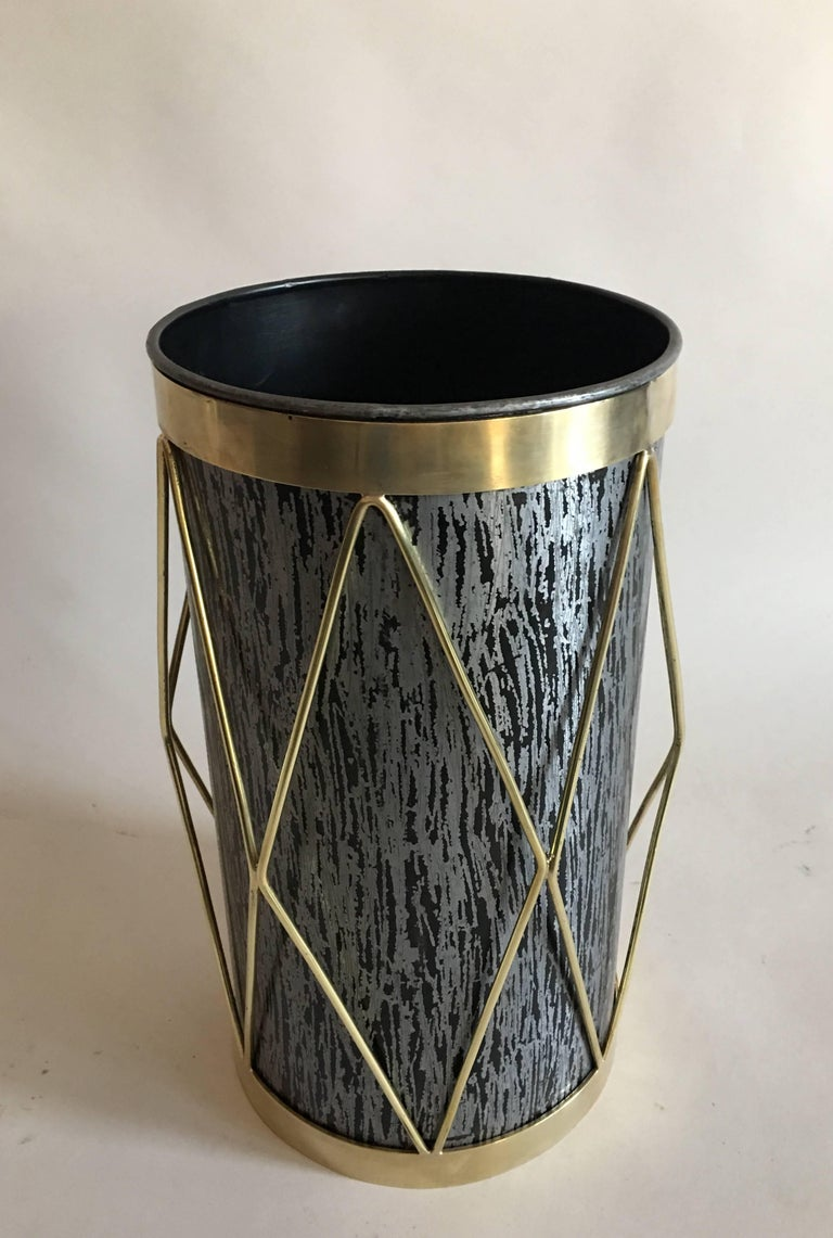 2 French Mid-Century Modern brass and steel umbrella stands, waste baskets / trash cans.   The pieces are composed of black stippled steel, and adorned with a dramatic brass overlay in a chevron or harlequin pattern.  Priced and sold individually.