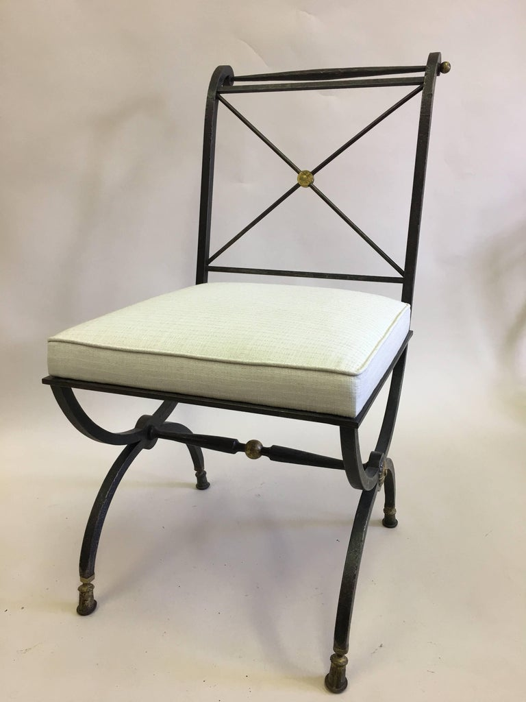 Elegant French modern neoclassical form hand-hammered wrought iron chair for desk, vanity or lounge by Gilbert Poillerat with the seat structure from a design by Andre Arbus.  The chair features a Classic Curule form (rounded X-form) leg