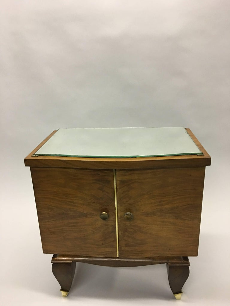 Elegant pair of French Mid-Century Modern neoclassical side tables/nightstands attributed to Rene Prou, circa 1940.   The pieces are composed of veneered fruitwood and cantilevered above the 4 legs. The front feet have brass sabots. A mirror top