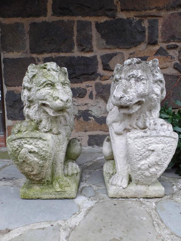 Pair of French 19th century garden statues of hand-carved stone lions with shields.   Each is crouched on their hind legs with an arm supporting an escucheon or shield upon which is cut a family coat of arms reflecting noble 18th century