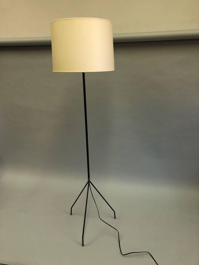 Elegant, sleek pair of hand-wrought iron floor lamps by Disderot. The standing lamps are delicately conceived with a slender iron stem that parts into a tripod base composed of thin, round iron bars that narrow to slim feet. The feet and details are