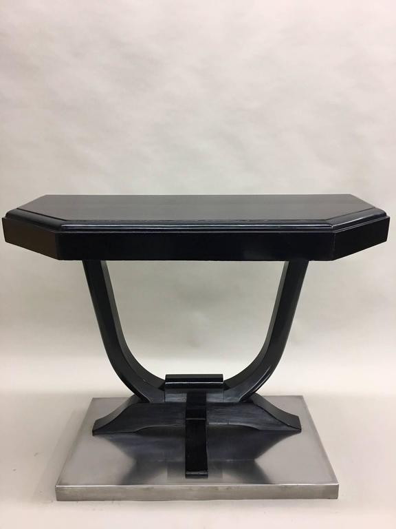 An elegant pair of French Art Deco ebonized mahogany consoles with the tops in a pentagonal pattern resting on a classic U form ebonized mahogany supports. The entire consoles rest on nickel steel bases forming a stunning, sober composition.