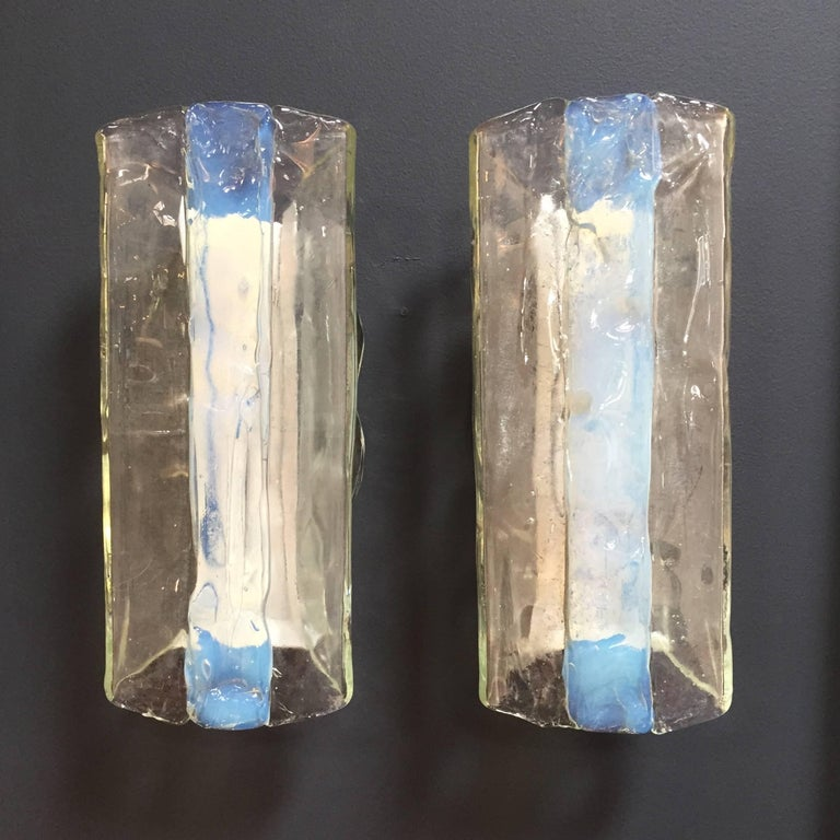 A gorgeous pair of Mid-Century Modernist sconces, both consisting of a folded iridescent handblown iridescent and clear Murano glass section, by Mazzega. White enameled back plates each fitted with two candelabra sockets each supporting up to 60W