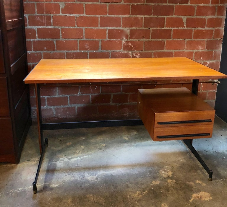 Midcentury Italian teak writing desk, 1950s. The table features an iron structure with brass ends. The piece is fully restored and in very good conditions.