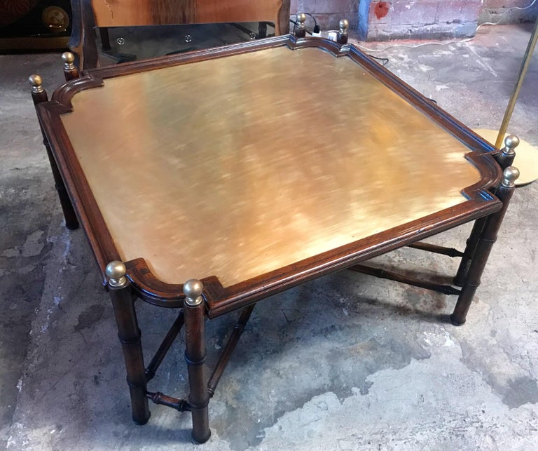 Large vintage coffee table of faux bamboo form wood base and removable tray top having a distinctive patinated brass top. This cocktail table has classic lines and solid brass finials mount on the top corners.