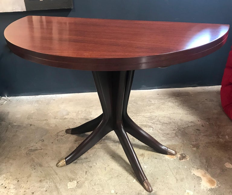 An Italian midcentury small sculptural console table on a sort of tripod with 4 wood legs leading and feet in brass suspending the small Rosewood console that becomes a nice round table (Diam. 40