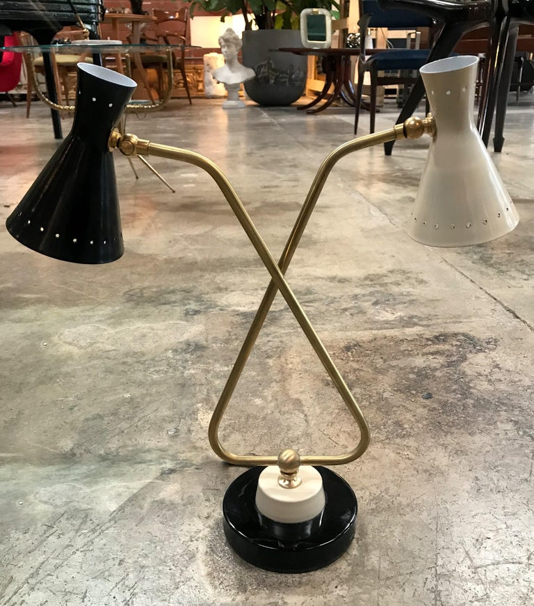 Midcentury double arms in brass table lamp with black and white round metal base. 
