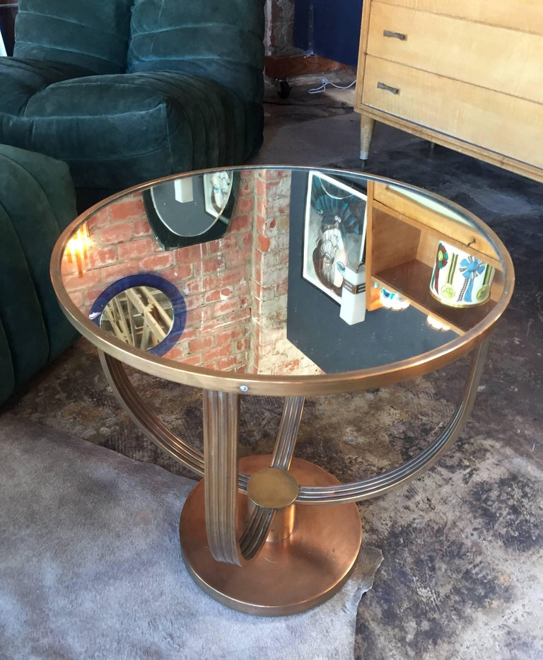 This smaller size cocktail table attributed to Jean Michel Frank has a very elegant Art Deco design: a round coffee table in slightly darkened brass. Four curved pieces separate the base and top. The top is fitted with a mirrored glass insert.