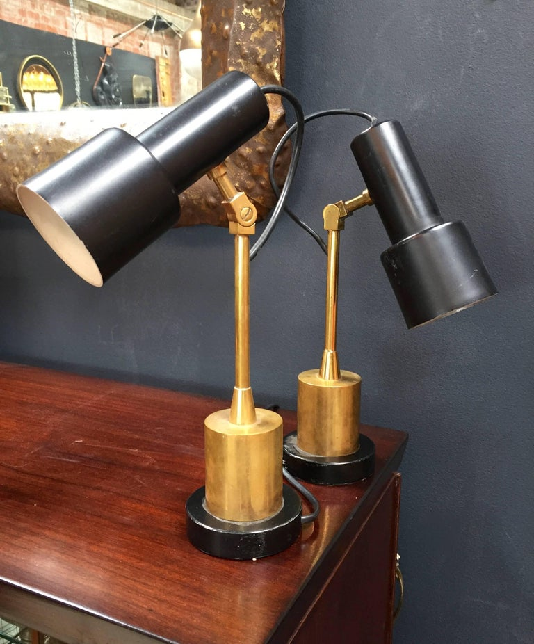 Pair of rare articulated Italian Stilnovo table lamps in brass with black metal round base.