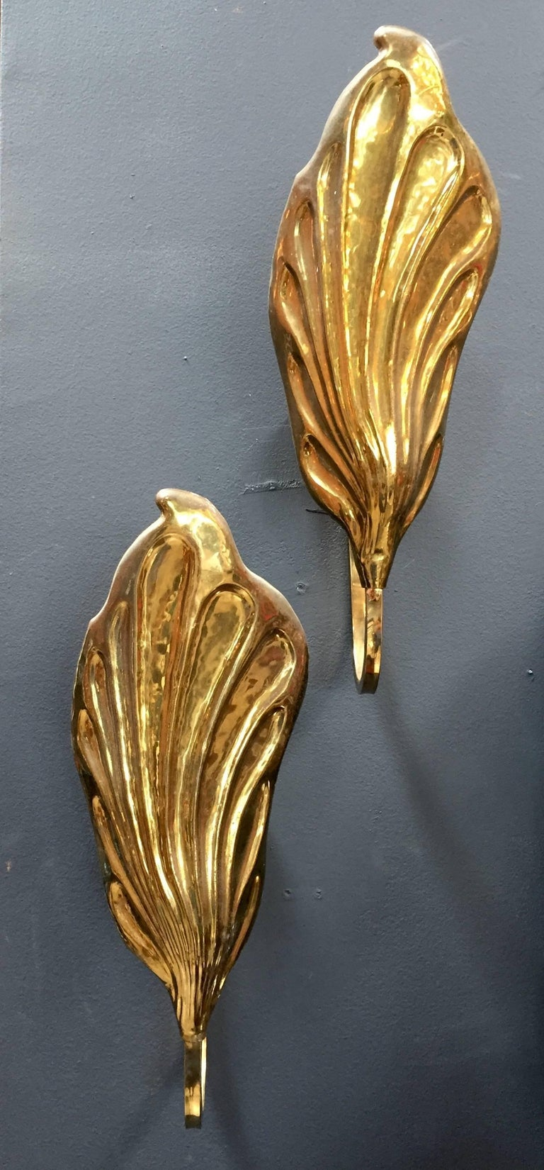 A pair of Tommaso Barbi wall lights in brass in the shape of leave. Italy, 1970s. Italian designer Tommaso Barbi is best known for whimsical furniture featuring organic forms, particularly brass leaf-shaped lamps.