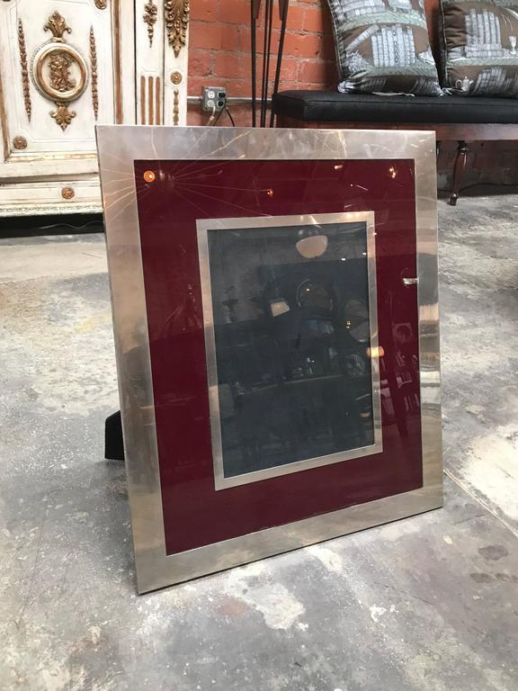 A chic 1970s modern Italian rectangular picture frame. Silver and burgundy color easel backing in black velvet.
