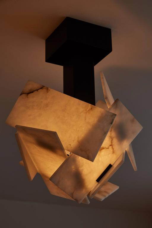Originally created in 1925 by Pierre Chareau. This ceiling lamp is a current production by Galerie MCDE of France.   On the end of one arm, the alabaster panels form an upside-down flower reflected on the ceiling in the shape of a star.  Finish: