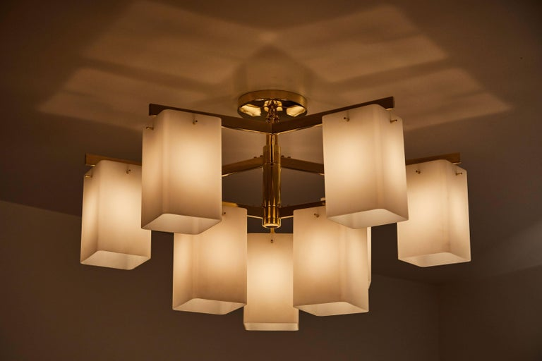 Rare chandelier with nine rectangular brushed satin glass shades and brass plated nickel. Manufactured by Stilnovo in Milan, circa 1960s. Takes nine E27 40w maximum bulbs. Wired for US junction boxes.