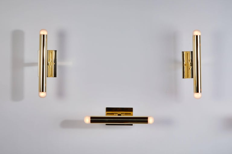 Set of four brass tubular sconces designed in Italy circa 1960s. Custom backplates, can be mounted horizontally or vertically. Wired for US junction boxes. Each sconce takes two E14 European candelabra. Priced and sold individually.