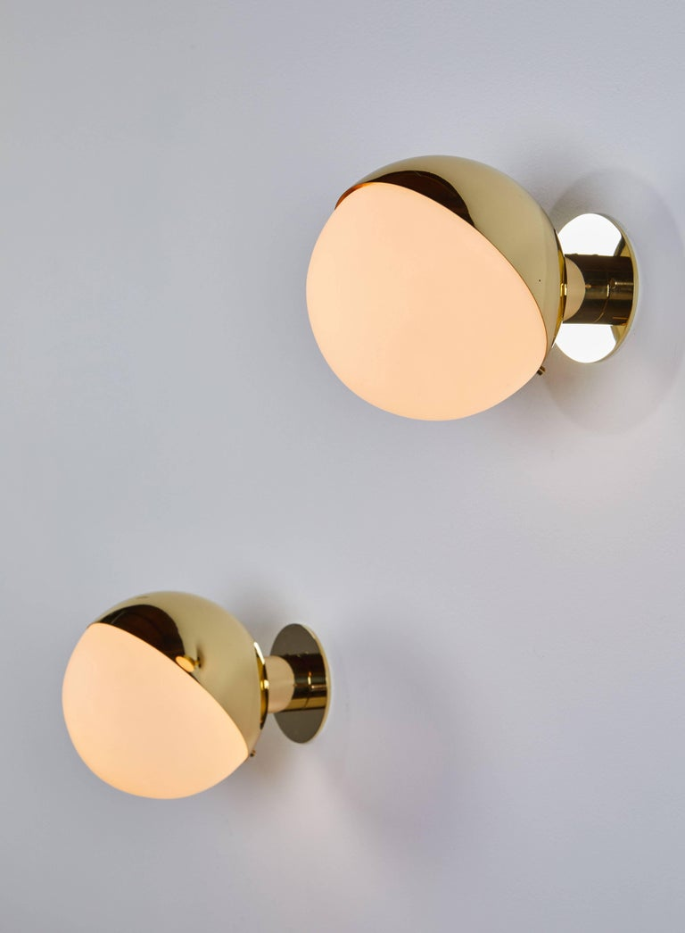 Pair of brass and opaline glass sconces manufactured by Stilnovo in Italy circa 1950's. Wired for US junction boxes. Custom backplates.  Each sconce takes one E27 75w maximum bulb
