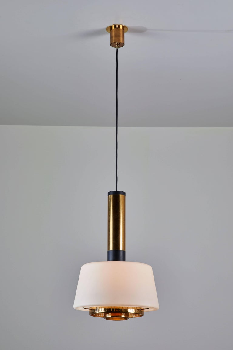 Two pendants manufactured by Stilnovo in Italy circa 1960s. Brushed satin glass diffusers, brass stem and hardware, original canopy with custom brass backplates. Rewired for US junction boxes. Overall drop can be adjusted. Height displayed is for