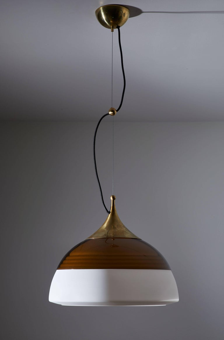 Two suspension pendant lights manufactured by Stilnovo in Italy, circa 1960s. Original brass armature with tinted plexiglass shades that rest on brushed satin glass diffusers. Original brass canopy. Rewired for US junction boxes. Overall drop can be