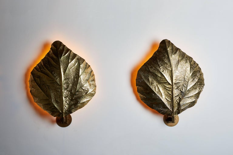 "Three iconic sculptural, hand-hammered brass ""leaf"" wall lights by Tommaso Barbi designed in Italy, circa 1970s. Rewired for US junction boxes. Each light takes one 100w e27 maximum bulb. Three lights available, one with a darker patina."