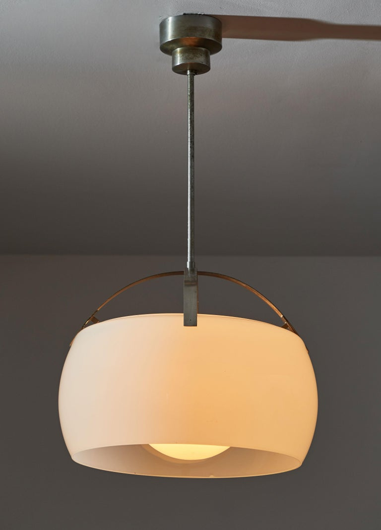 Two Clinio Pendants by Vico Magistretti for Artemide. Designed and manufactured in Italy circa 1960's. Brushed nickel plated brass hardware and canopy. Opaline glass diffusers. Rewired for US junction boxes. Each light takes one E27 100w maximum