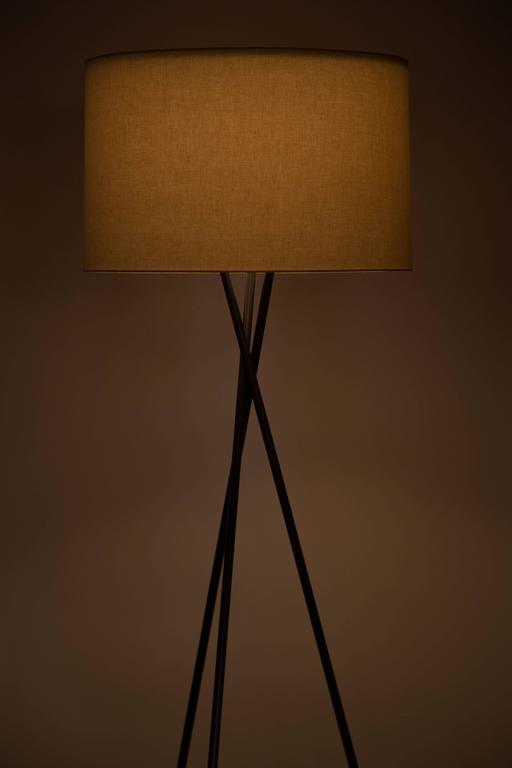 Bronze tripod floor lamps with custom shades.