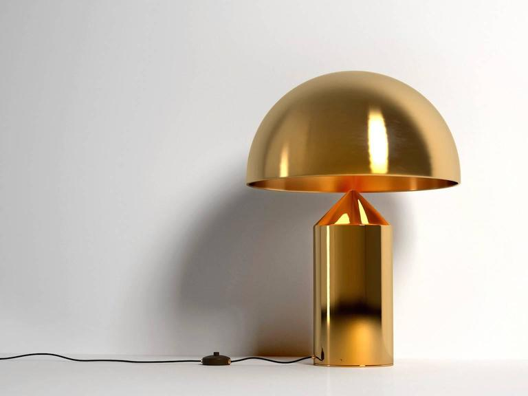 Iconic Atollo model 233 table lamp originally designed by Vico Magistretti for Oluce in 1977. This current production provides direct light as a table or bedside lamp. Comes in a gloss black painted aluminum finish or satin gold galvanic finish or