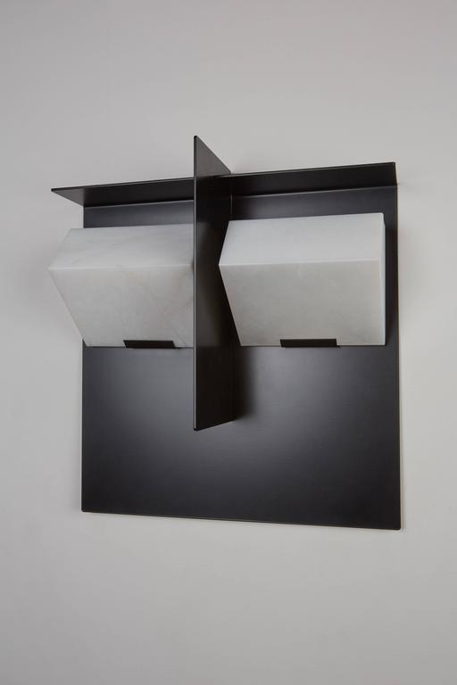 "Originally designed in 1923, this current production of the Pierre Chareau ""Mask"" wall lamp is composed of two blocks of alabaster mounted side-by-side on a painted black metal structure  and separated by a metal leaf. Hue of alabaster varies in"