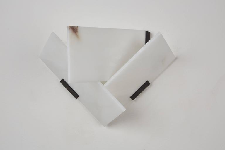 Originally designed in 1924, this current production of the Fly wall lamp by Pierre Chareau is composed of three rectangular alabaster panels. Hue of alabaster varies in each light. Comes with a certificate of authenticity. Each lights takes an E14