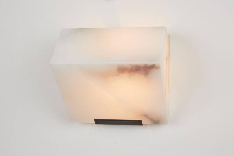 Originally designed in 1923 this current production by Galerie MCDE of France of the simple sloping wall lamp by Pierre Chareau is composed of a single block of alabaster. This wall lamp is also available in double or triple blocks. Hue of alabaster