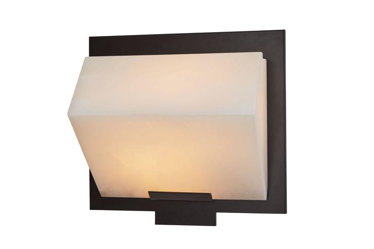 Originally designed in 1923 this current production of the simple sloping wall Lamp by Pierre Chareau is composed of a single block of alabaster fastened to a black stainless steel mount. Hue of alabaster varies in each light. Comes with a